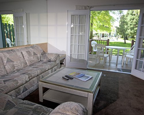 A well furnished living room with queen pull out sofa and a patio.