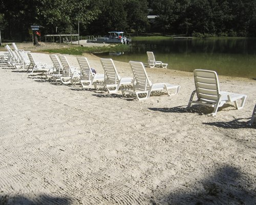Beach view of chaise lounge chairs facing the lake.