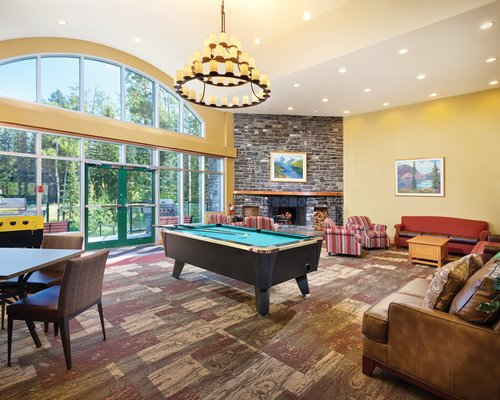 An indoor recreation room with pool table and an outside view.