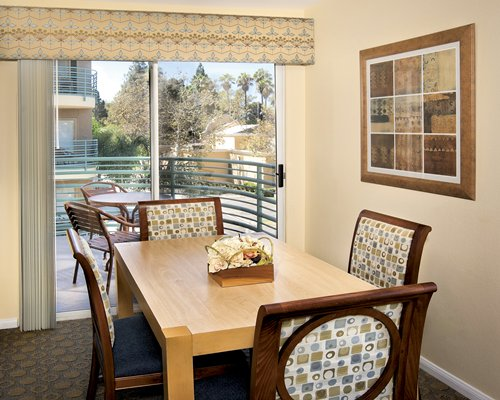 A well furnished dining area alongside a balcony with patio furniture.
