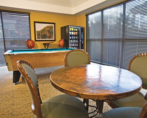 An indoor recreation area with a pool table and an outside view.