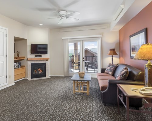 A well furnished living room with television television fire in the fireplace and balcony with patio chairs.