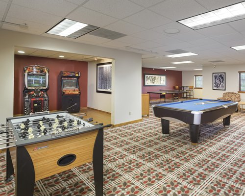 An indoor recreation room with pool foosball table and arcade games.
