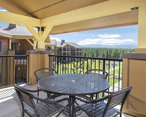 Outdoor dining on the balcony with view of wooded area.