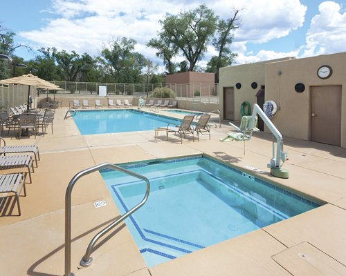 An outdoor swimming pool and kiddie pool with chaise lounge chairs and patio furniture.