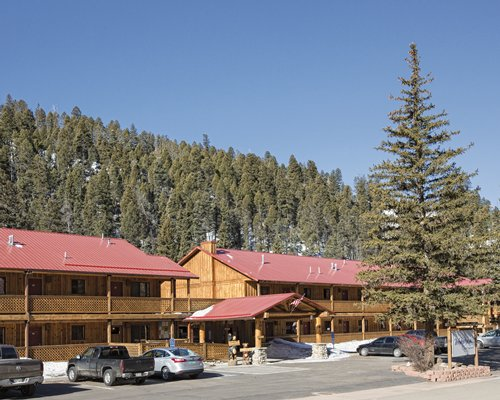 A street view of multiple resort units with pine trees.