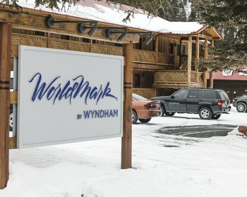 Signboard of Worldmark resort covered in the snow alongside the parking lot.