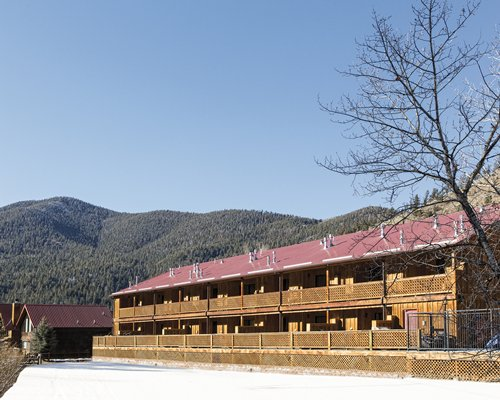 An exterior view of the Worldmark Red River resort alongside the mountains.