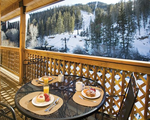 A balcony dining area alongside the snow covered pine tree mountains.