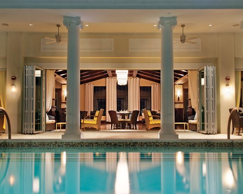 An indoor swimming pool alongside a well furnished lounge area.