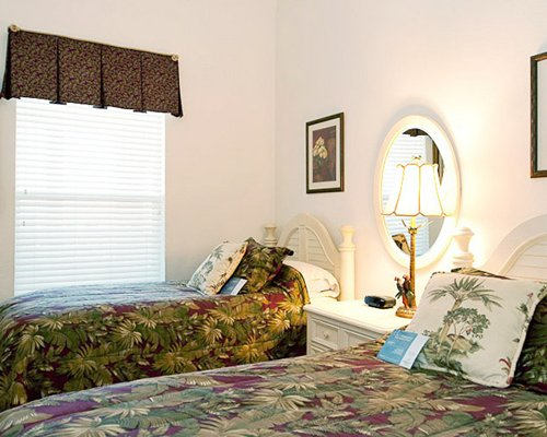 A well furnished bedroom with two king beds and an outside view.