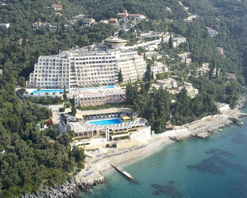 An aerial view of Sunshine Rhodes resort surrounded by trees alongside the sea.