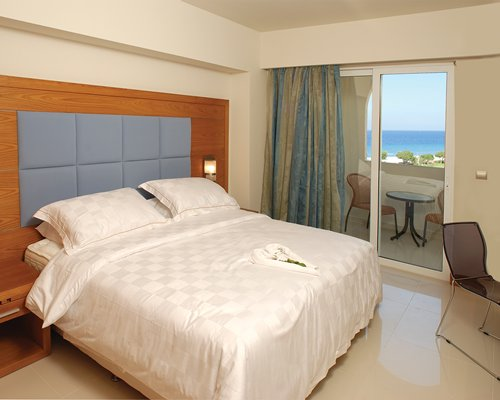 A well furnished bedroom with balcony patio furniture and sea view.