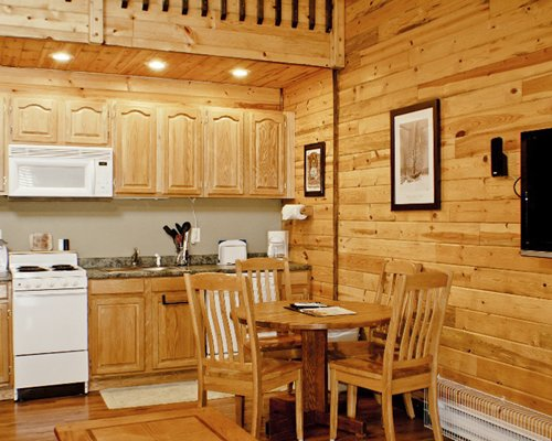 A well equipped kitchen with a wooden dining area.