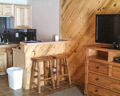 A well equipped kitchen with a breakfast bar and television.