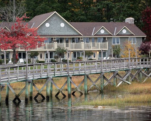 Exterior view of Sheepscot Harbour Village & Resort with a wooden pier on the water.
