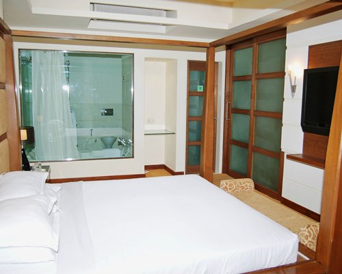 A well furnished bedroom with a television alongside a bathroom.