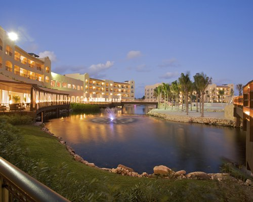 An exterior view of multi story resort units alongside the waterfront.