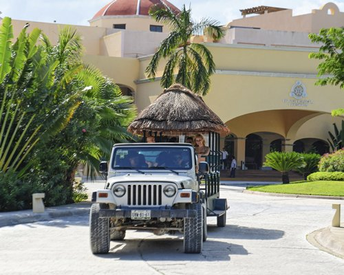 Guests riding on a jeep with a thatched coach from the Hacienda Tres Rios main building.