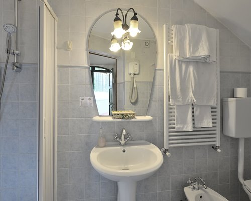 A bathroom with a shower and single sink vanity.