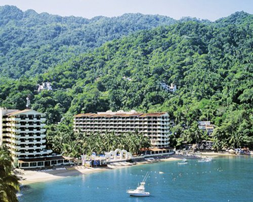 Exterior view of Barcelo La Jolla de Mismaloya at a wooded area alongside the beach with a boat.