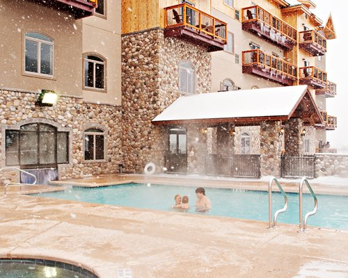 View of multiple balconies at Tamarack Club with outdoor swimming pool and hot tub.