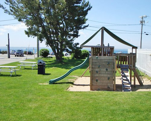 An outdoor picnic area with barbecue grills and a playscape.