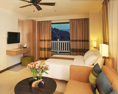 A well furnished bedroom with queen bed living area television and balcony.