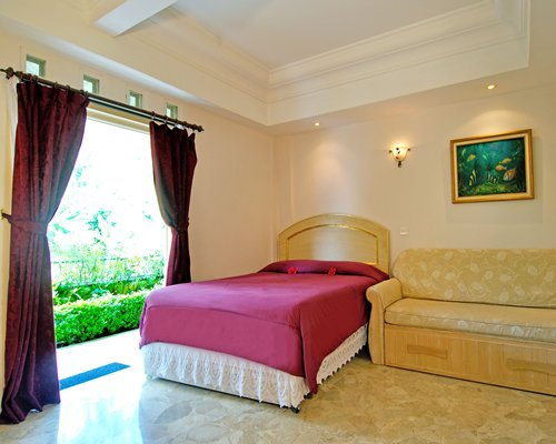 A well furnished bedroom with queen bed and a patio.