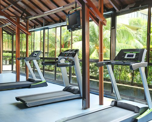 An indoor fitness center with a television and outside view.