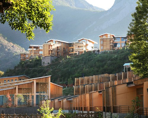 An exterior view of multi story resort units with wooded area alongside the mountains.