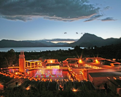 Exterior view of HIVC at Lugu Lake Mosuo Home Hotel alongside the waterfront at night.