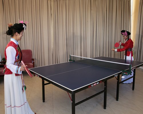 A view of people playing ping pong.