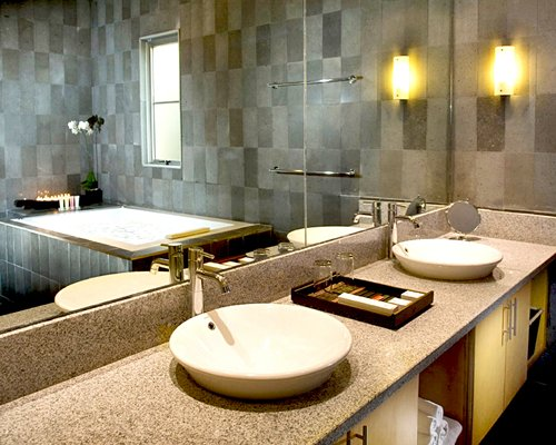 A bathroom with bathtub and double sink vanity.