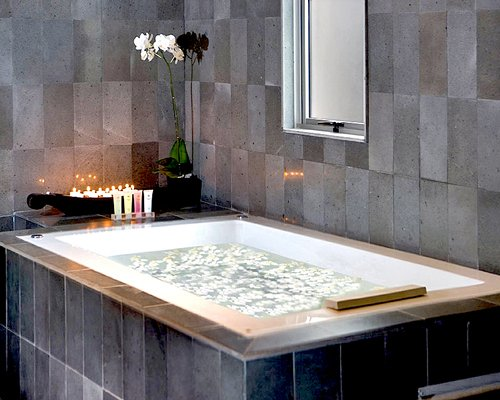 A bathtub set in granite tile.