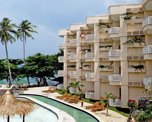 An exterior view of the multi story condo and a pool with chaise lounge chairs and thatched sunshades.