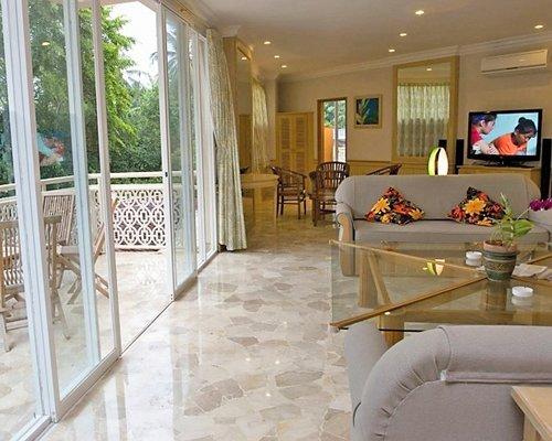An open plan living room and dining area with a television and balcony.