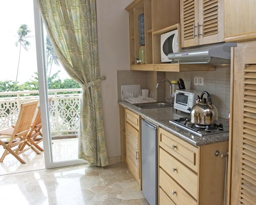 A well equipped kitchen with a microwave oven alongside a balcony.