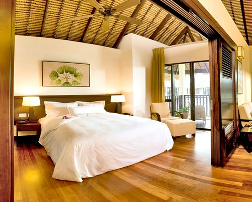 A well furnished bedroom with two lamps and a balcony with patio.
