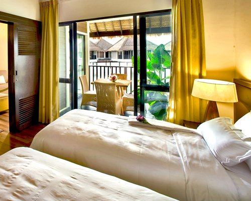 A well furnished bedroom with two twin beds and a balcony with patio furniture.