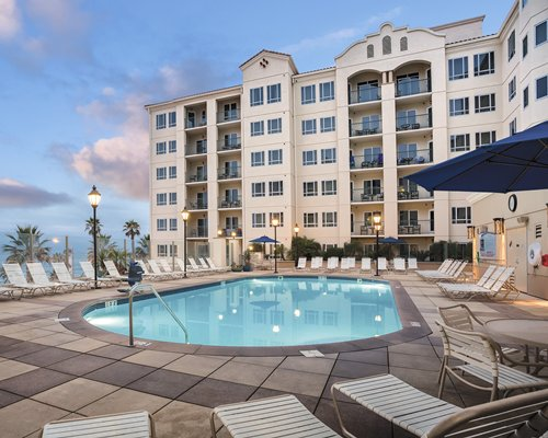 Wyndham Oceanside Pier Resort with an outdoor swimming pool chaise lounge chairs and sunshades.