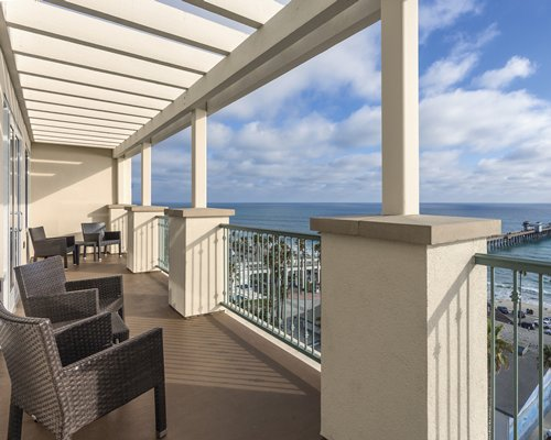 A balcony with patio furniture and the ocean view.
