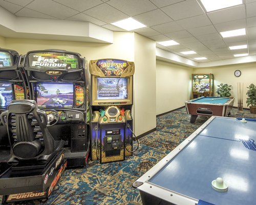 An indoor recreational room with a pool table and arcade games.