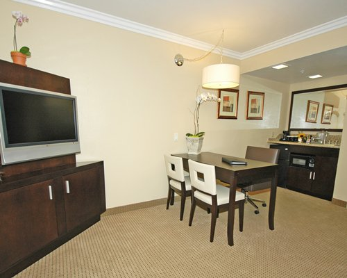 A well furnished living room with television dining area and open plan kitchen.