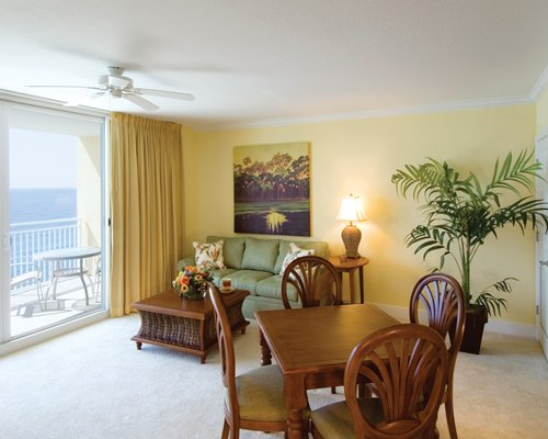 A well furnished living room with dining area balcony and patio chairs.
