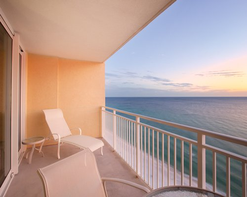 View of chaise lounge chairs in the balcony with the beach view.