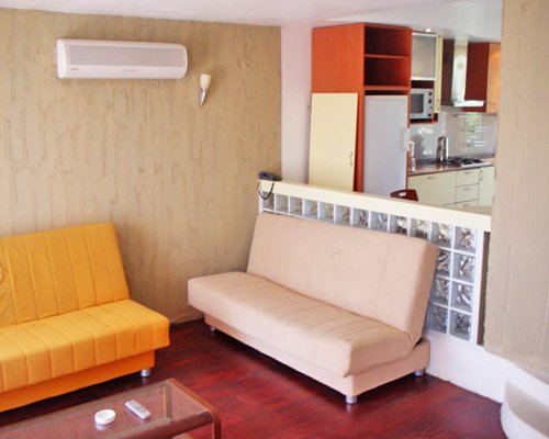 A well furnished living room with open plan kitchen.