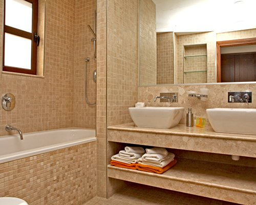 A bathroom with a shower bathtub and double sink.