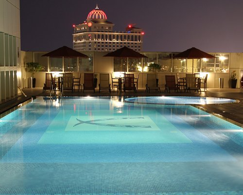 Night view of an outdoor pool with chaise lounge chairs and umbrellas alongside the Ivory Grand Hotel Apartments.