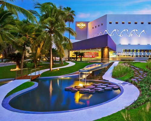 A scenic exterior view of Hard Rock Vallarta resort with the water fountain at dusk.